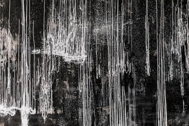 Pintura abstracta: manchas y salpicaduras de pintura blanca sobre un fondo oscuro