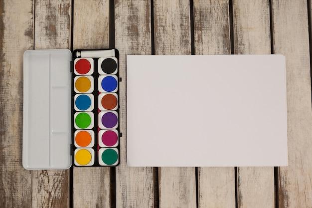 Pintura de acuarela y papel blanco sobre mesa de madera