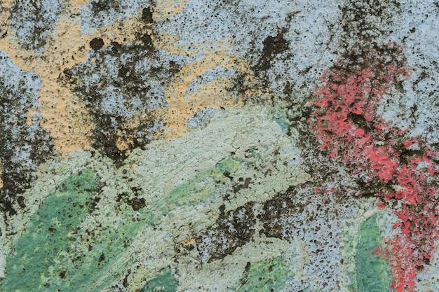 Pintura agrietada en un muro de piedra.