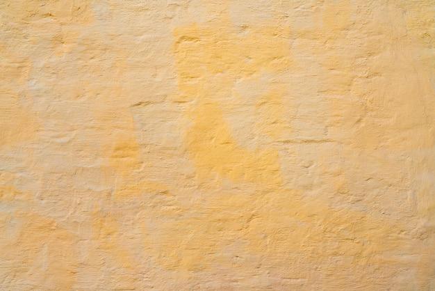 Pintura amarilla y beige en la pared de la casa.