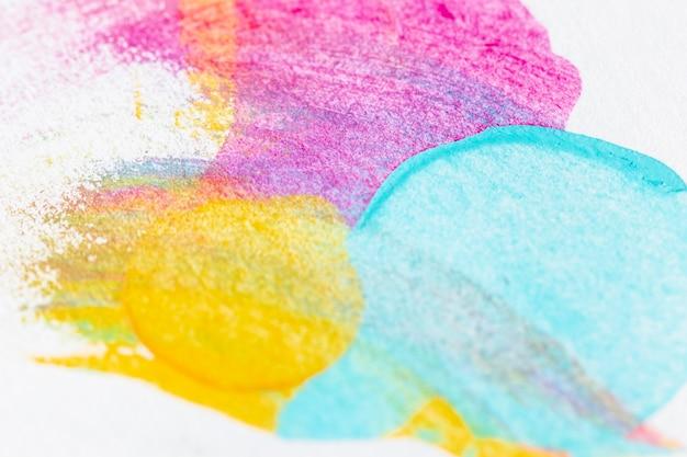 Pintura azul, amarilla y rosa sobre fondo blanco.