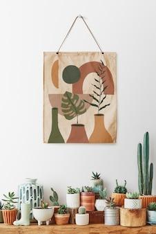 Pintura colgando sobre un estante lleno de cactus y suculentas.
