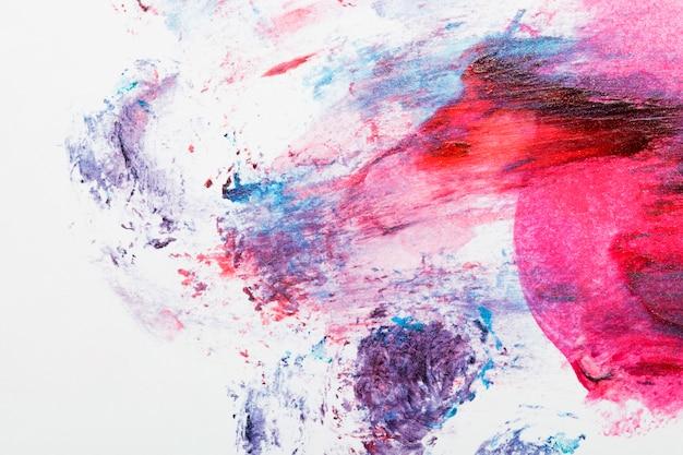 Pintura colorida dispersada sobre fondo blanco