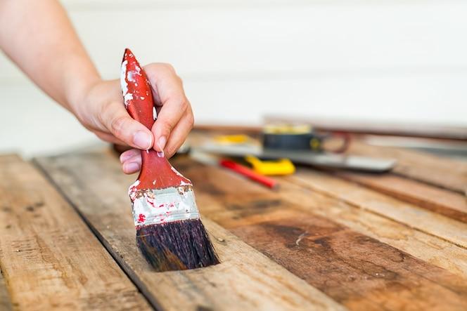 Pintura de la mano del trabajador madera, protección de la madera para influencias exteriores, intemperie