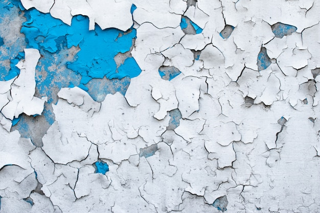 Pintura descascarada en un muro de hormigón. fondo abstracto pintado azul y blanco, superficie agrietada del grunge, textura del modelo.