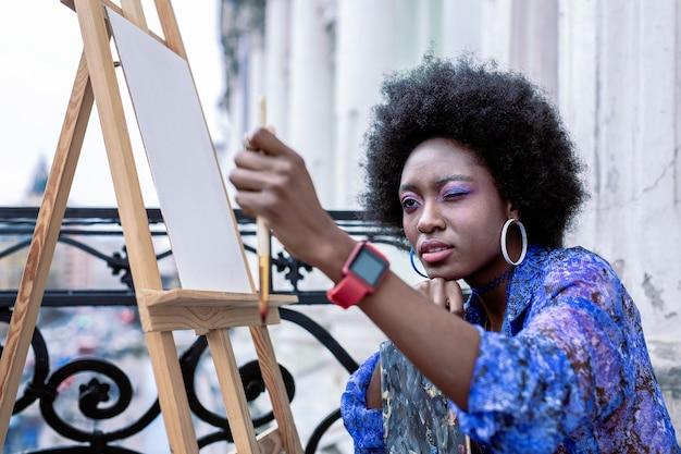 Pintura exterior. artista elegante y talentoso con maquillaje brillante y vistiendo un vestido azul pintando afuera