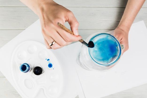 Pintura femenina de la mano en el tarro de cristal con el cepillo de pintura sobre el escritorio de madera