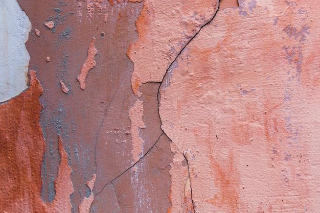 Pintura y grietas en el muro de hormigón.