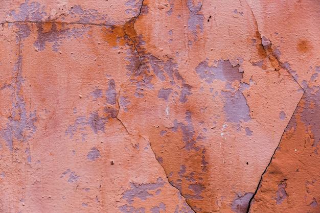 Pintura y grietas en la superficie de la pared de cemento.