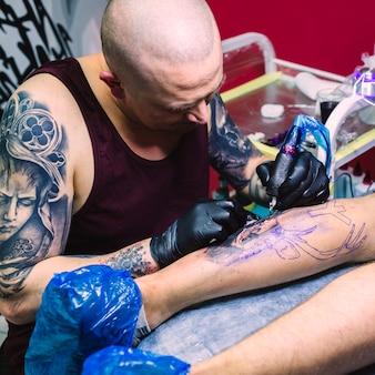 Pintura maestra del tatuaje en la pierna con la máquina