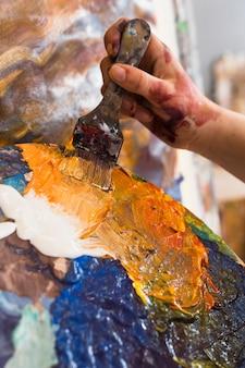 Pintura de la mano de la persona con pintura desordenada y pincel.