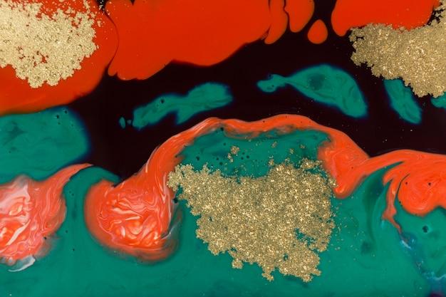 Pintura de mármol rojo, verde y dorado mezclado.