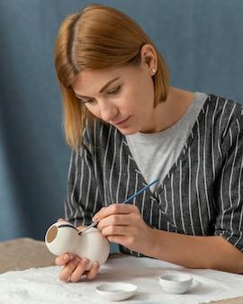 Pintura de mujer de tiro medio con pincel