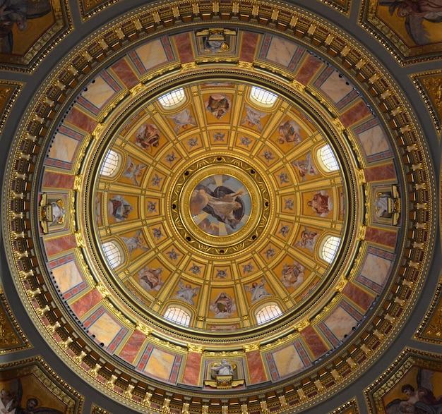 Pintura mural en la cúpula de una iglesia católica con imágenes religiosas en color de santos y escenas bíblicas en color