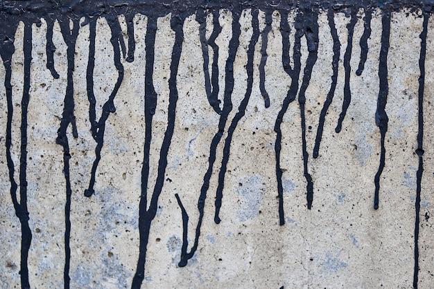 La pintura negra actual en una pared descolorida áspera.
