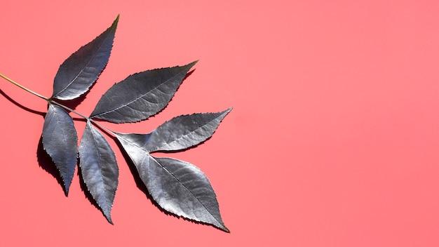 Pintura plateada de hojas y fondo rosa espacio de copia