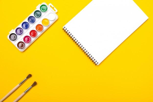 Pinturas de acuarela y pinceles con lienzo para pintar con copyspace