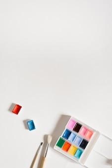 Pinturas de acuarela en zanjas y pinceles sobre un blanco