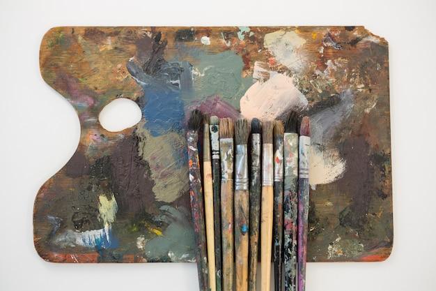 Pinturas de acuarelas y pinceles en la paleta contra el fondo blanco.