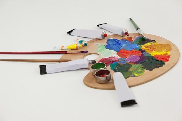 Pinturas de acuarelas y pinceles en la paleta contra la superficie blanca