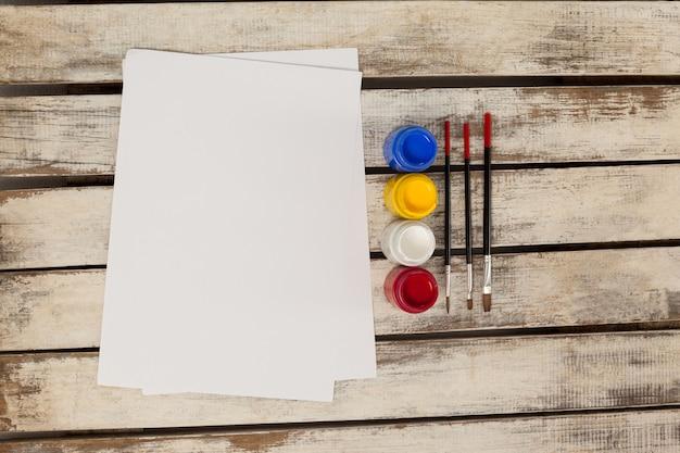 Pinturas de acuarelas, pinceles y papel blanco sobre mesa de madera