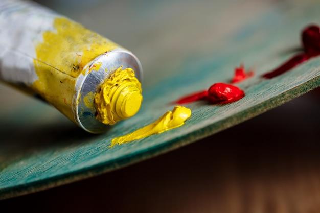 Pinturas al óleo rojas y amarillas en paleta sobre pared de madera