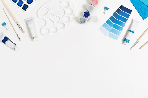 Pinturas azules clásicas y pinceles fondo blanco con espacio para texto.