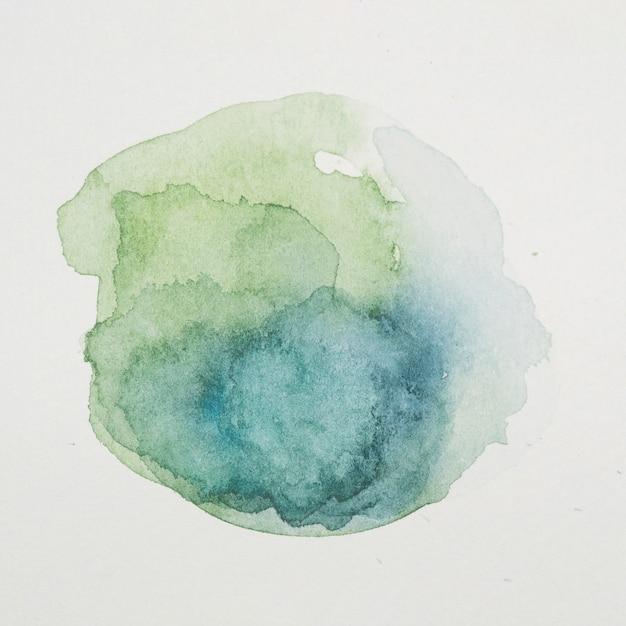 Pinturas azules y verdes en forma de círculo sobre papel blanco.