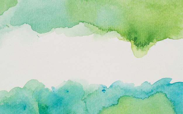 Pinturas azules y verdes sobre papel blanco.
