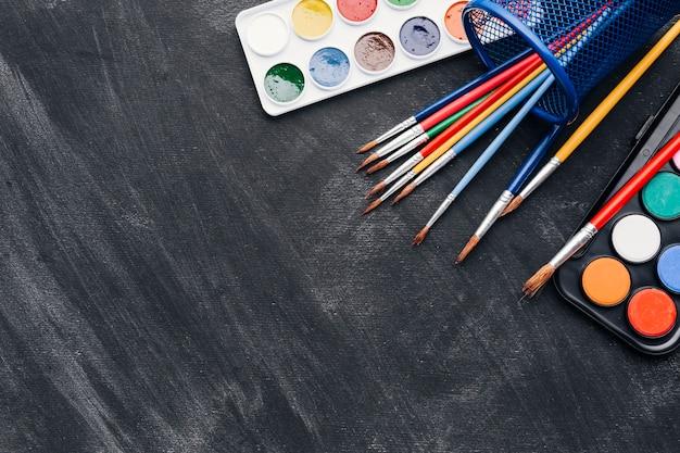 Pinturas brillantes y pinceles sobre fondo gris.