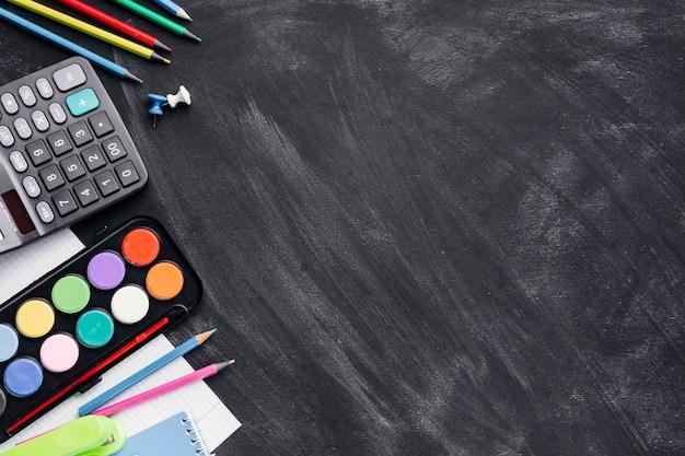 Pinturas de colores, calculadora y lápices sobre fondo gris