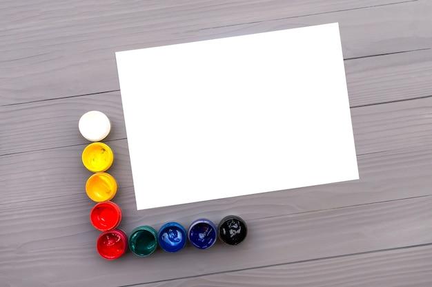 Pinturas de colores y hojas de papel
