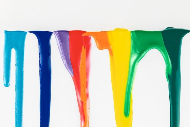 Pinturas coloridas goteando sobre fondo blanco.