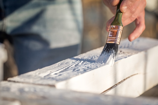 Pinturas de manos masculinas con pintura blanca sobre madera, concepto de pintura, primer plano, lugar para el texto