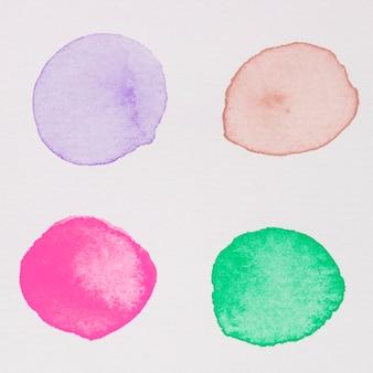Pinturas moradas, rojas, rosadas y verdes sobre papel blanco.