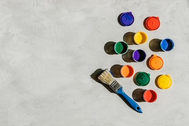 Pinturas multicolores en frascos redondos y pincel sobre hormigón gris.