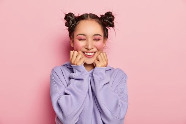 Pinup mujer japonesa con dos moños peinados que toca las mejillas, tiene la piel suave, usa maquillaje rosado vivo, piercing en la nariz, usa sudadera, sonríe positivamente, aislado sobre fondo rosa.