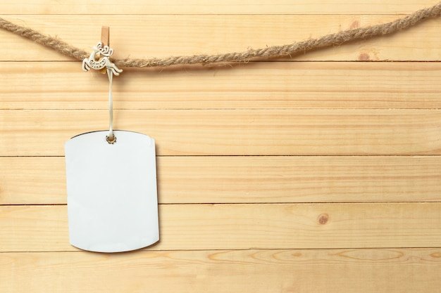 Pinza para la ropa colgada con papel en blanco sobre fondo de madera