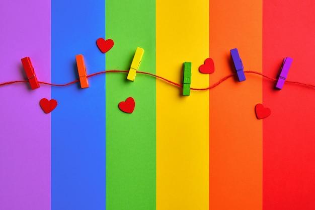 Pinzas de madera de colores del arco iris y corazones rojos sobre fondo de bandera del arco iris