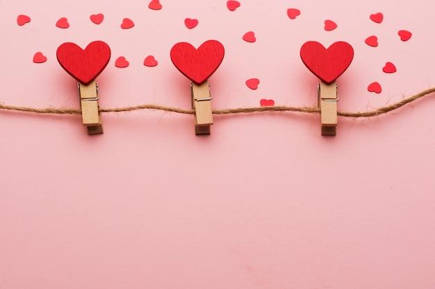 Pinzas de madera con corazones en una cuerda sobre un fondo rojo.