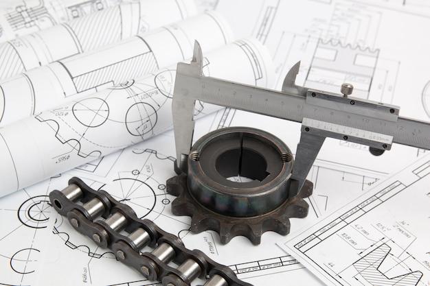 Pinzas, piñones, cadenas industriales y dibujos de ingeniería de piezas y mecanismos industriales.