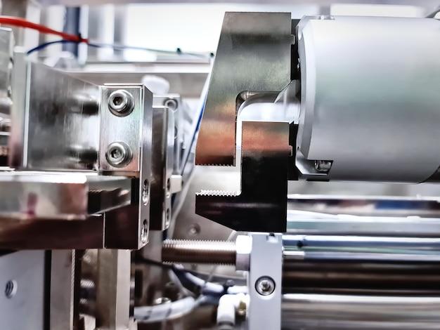 Pinzas robóticas brillantes de primer plano en equipos de maquinaria