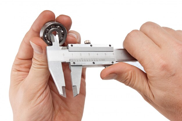 Pinzas con rodamiento en mano aislado sobre superficie blanca