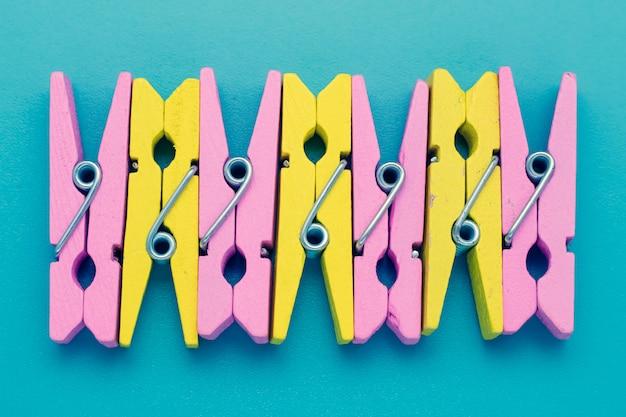 Pinzas para la ropa amarillas y rosadas en una superficie azul.