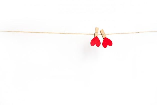Pinzas para la ropa corazones colgando de la cuerda y aislados en blanco.
