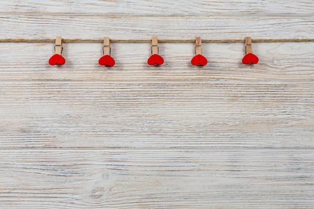 Pinzas para la ropa y corazones de madera roja en una cuerda como concepto del día de san valentín