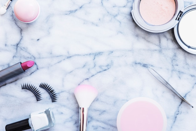 Pinzas; rubores esmalte de uñas; lápiz labial; polvo compacto y pestañas sobre fondo de mármol con textura.