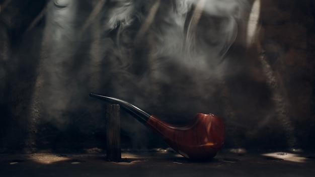Pipa para fumar material de cerezo sobre fondo de acero con humo de tabaco y rayos de luz