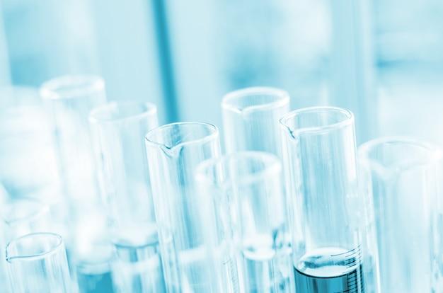 Una pipeta que deja caer la muestra en un tubo de ensayo, fondo de ciencia abstracta