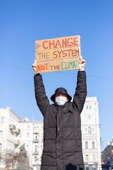 Piquete de protesta en solitario en la plaza de la ciudad salva el concepto del planeta con el lema cambiar el sistema, no el clima